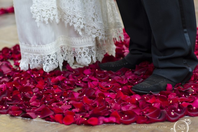 Sedona bride and groom stand on a beautiful floral carpet made especially for their romantic and intimate wedding in Arizona