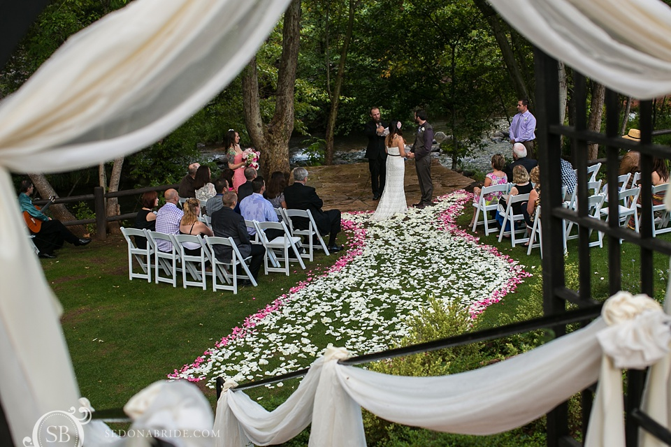 View of ceremony through gorgeous floral and decor on Oak Creek Sedona