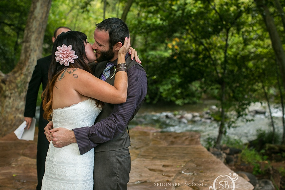 The bride and groom kiss to tie the knot on Oak Creek in Sedona