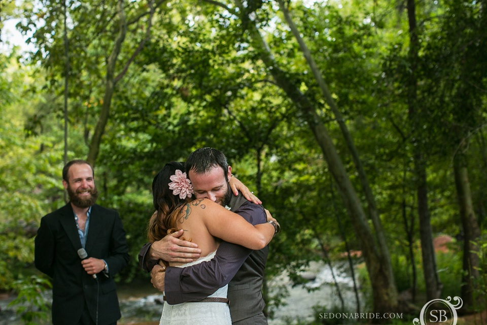 The bride and groom embrace after tying the knot on Oak Creek in Sedona